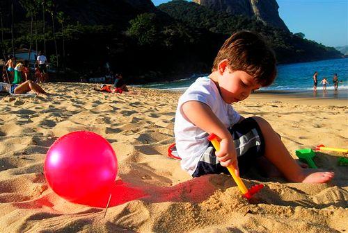 Rafa estava tão concentrado em sua brincadeira que não resisti: deitei na areia para registrar esse momento tão fofo! De quebra, aproveitei a bola rosa para dar um contraste que deixei a foto ainda mais divertida!